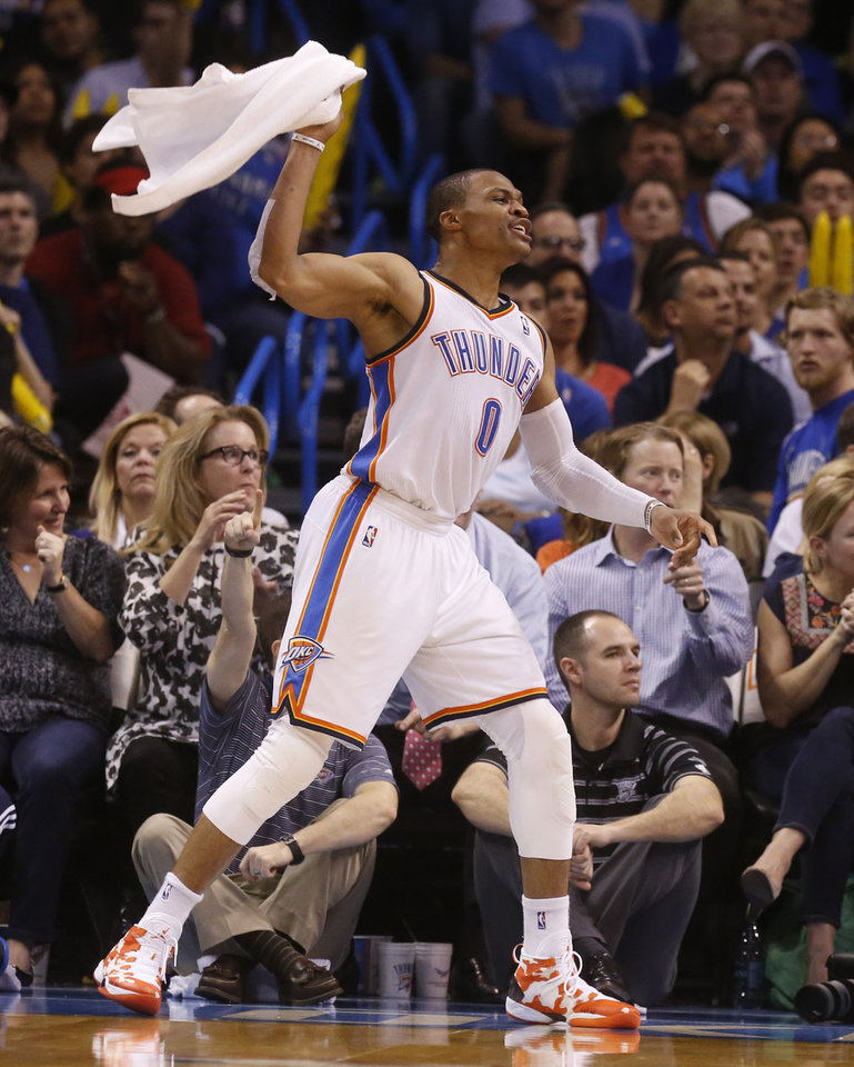 Photo - Oklahoma City Thunder guard Russell Westbrook (0) waves a towel on the sidelines during the third quarter of an NBA basketball game against the Houston Rockets in Oklahoma City, Tuesday, March 11, 2014. Oklahoma City won 106-98. (AP Photo/Sue Ogrocki)