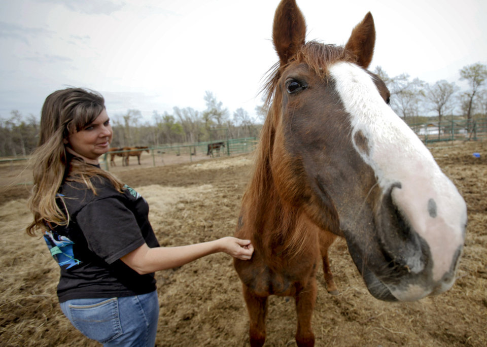 Photo - HORSE RESCUE: Horse rescuer Natalee Cross pets a rescued horse on Thursday, April 16, 2009, in Jones, Okla. The horse is one of the 20 horses that were rescued in February from an individual in Garvin County.  Photo by Chris Landsberger, The Oklahoman  ORG XMIT: KOD