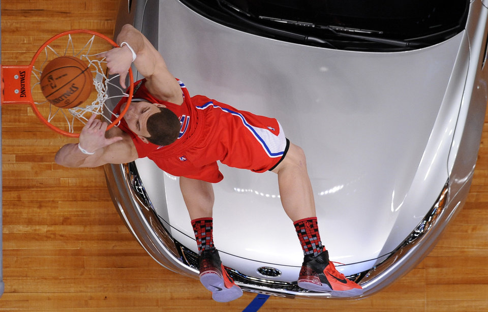 Photo - Los Angeles Clippers' Blake Griffin dunks over a car during the Slam Dunk Contest at the NBA basketball All-Star weekend, Saturday, Feb. 19, 2011, in Los Angeles.  (AP Photo/Mark J. Terrill)