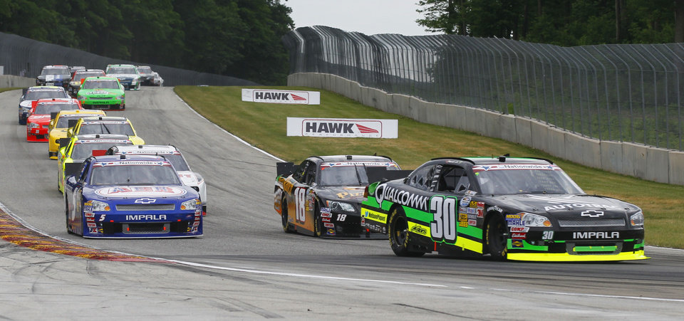 Photo -   Nelson Piquet Jr., (30) leads a group of cars into a turn during the NASCAR Nationwide Series Sargento 200 auto race at Road America in Elkhart Lake, Wis, Saturday, June, 23, 2012. Piquet Jr. went on to win the race. (AP Photo/Jeffrey Phelps)