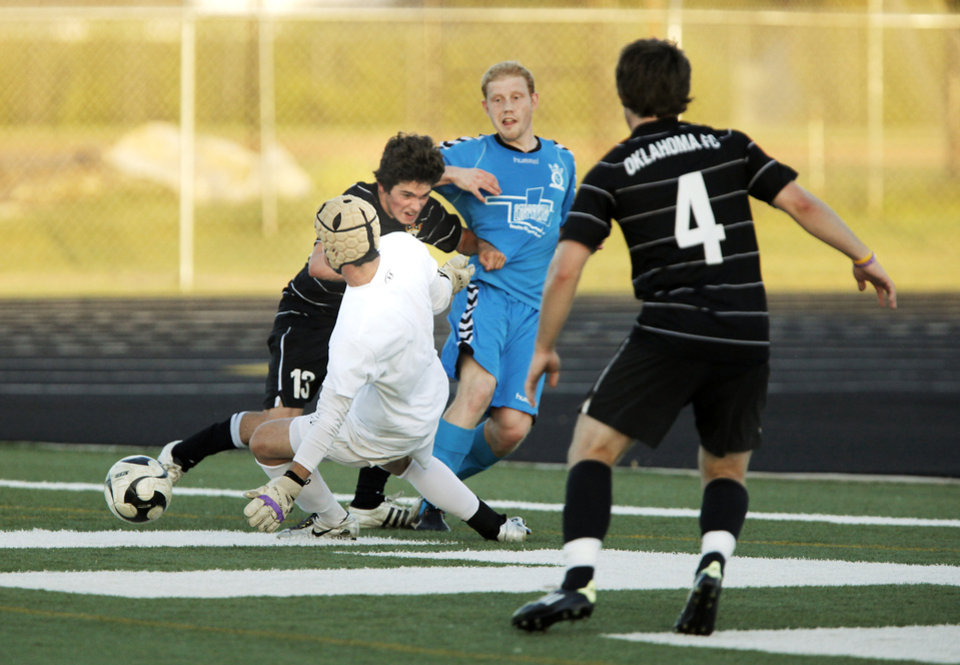 OKC FC PROFESSIONAL SOCCER: Oklahoma City FC goalkeeper Evan Helker slides through defender Jackson Gray (left) to block a shot in a scrimmage with Oklahoma City FC's premier development league team on June 17, 2013. Photo by KT KING, The Oklahoman