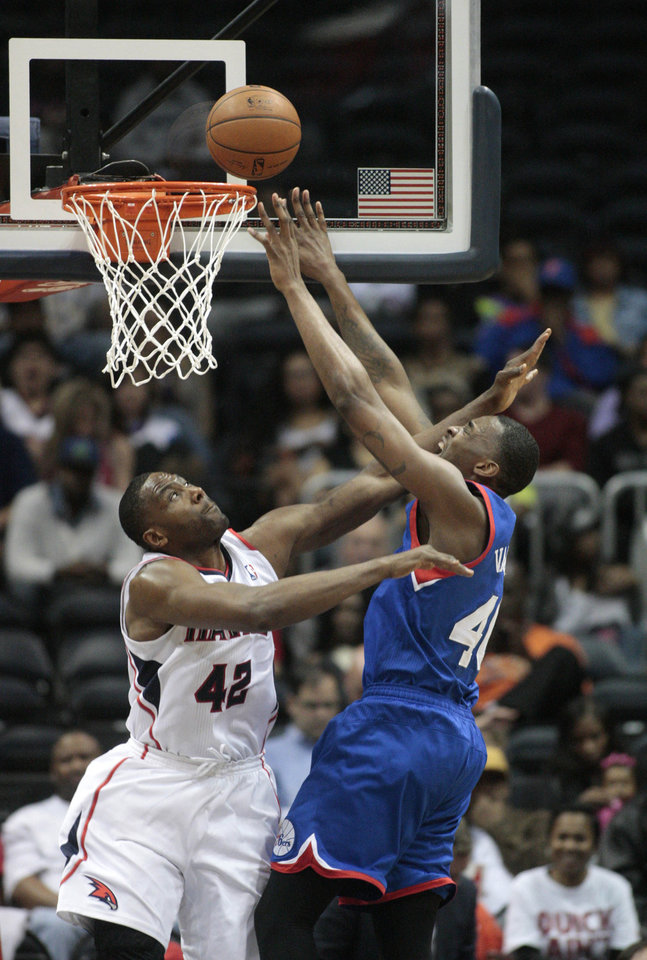 Photo - Philadelphia 76ers forward Jarvis Varnado (40) attempts a shot and is fouled by Atlanta Hawks forward Elton Brand (42) in the first half of an NBA basketball game Monday, March 31, 2014, in Atlanta. (AP Photo/Jason Getz)