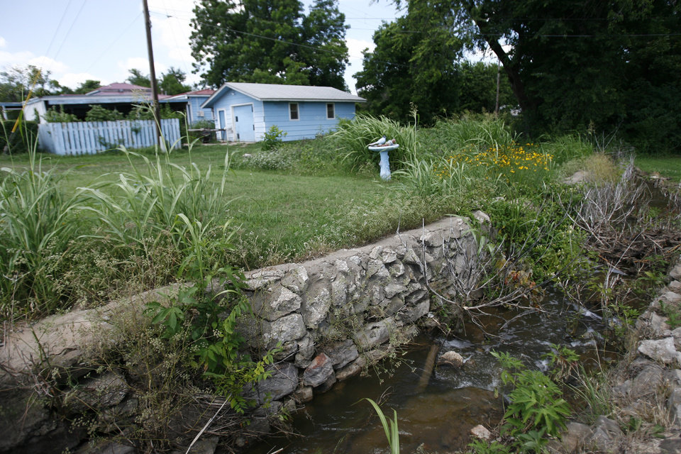 Photo - The house owned by Melvin Morris sits beside the creek that comes from the Cushing Superfund site. Clean up is taking place at Superfund Site located in Cushing, Okla. Tuesday June 22, 2009. Photo by Mitchell Alcala, The Oklahoman ORG XMIT: KOD
