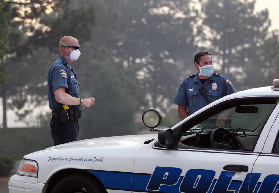 Photo - Colorado Springs police officers wear masks for smoke as they man a roadblock to an evacuated area of forest, ranches and residences, in the Black Forest wildfire area, north of Colorado Springs, Colo., on Thursday, June 13, 2013.  The blaze in the Black Forest area northeast of Colorado Springs is now the most destructive in Colorado history, surpassing last year's Waldo Canyon fire, which burned 347 homes, killed two people and led to $353 million in insurance claims. (AP Photo/Brennan Linsley)