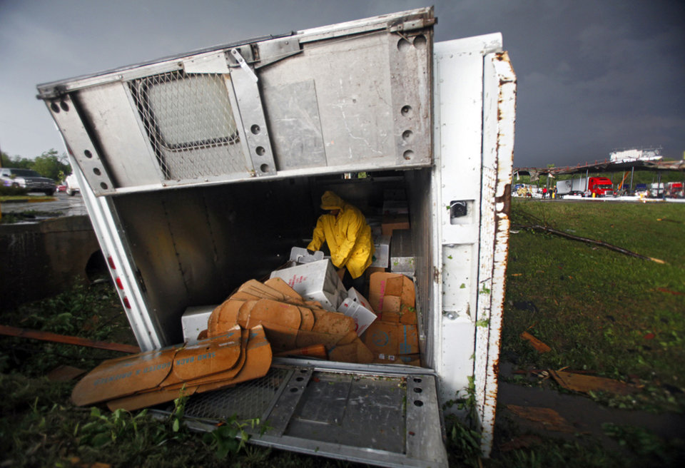 Photo - STORM DAMAGE / INTERSTATE 40:  Frito-Lay driver looks through his inventory in his turned over delivery truck after a tornado damaged the area around I-40 and Choctaw Road on Monday, May 10, 2010, in Oklahoma City, Okla.  Photo by Chris Landsberger, The Oklahoman  ORG XMIT: KOD