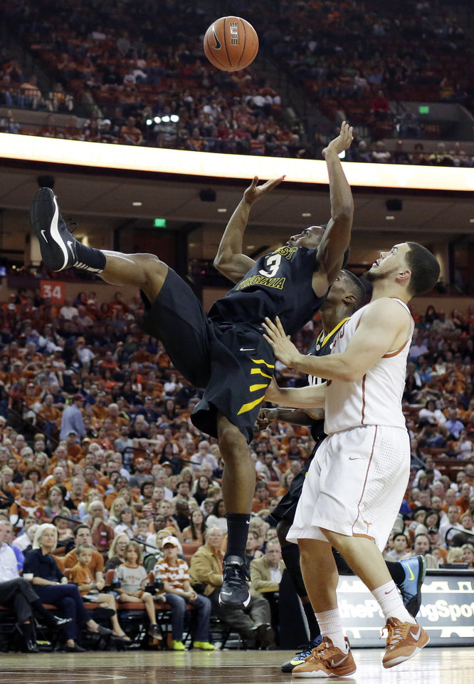 Photo - West Virginia's Juwan Staten (3) shoots off balance in front of Texas' Javan Felix during the second half of an NCAA college basketball game Saturday, Feb. 15, 2014, in Austin, Texas. Texas won 88-71. (AP Photo/Eric Gay)
