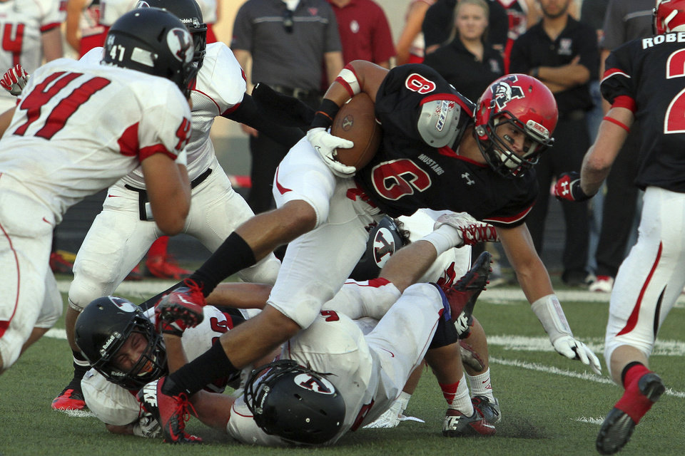 Photo - Mustang's Joey Snodgrass dives for more yards during the Mustang - Yukon High School football  season opener Friday night at Bronco Stadium in Mustang. Photo by Hugh Scott, for the Oklahoman