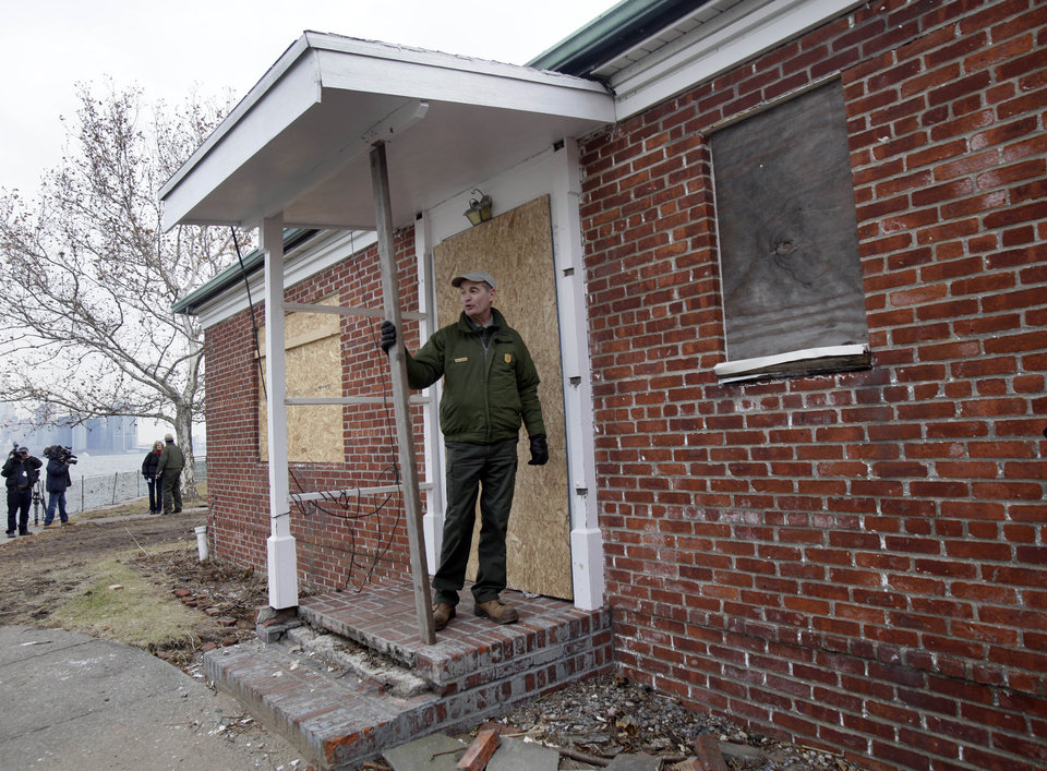 Photo - David Luchsinger, superintendent of Statue of Liberty National Monument, and last resident of Liberty Island, poses for a photo at the back door of his Superstorm Sandy-damaged home, on Liberty Island in New York, Friday, Nov. 30, 2012. Tourists in New York will miss out for a while on one of the hallmarks of a visit to New York, seeing the Statue of Liberty up close. Though the statue itself survived Superstorm Sandy intact, damage to buildings and Liberty Island's power and heating systems means the island will remain closed for now, and authorities don't have an estimate on when it will reopen. (AP Photo/Richard Drew)