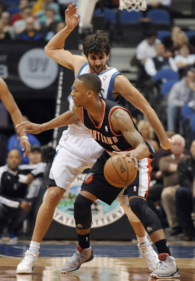 Minnesota Timberwolves' Ricky Rubio, rear, of Spain, defends Portland Trail Blazers' Damian Lillard (0) during first quarter of an NBA basketball game Monday, Feb. 4, 2013, in Minneapolis. (AP Photo/Hannah Foslien)
