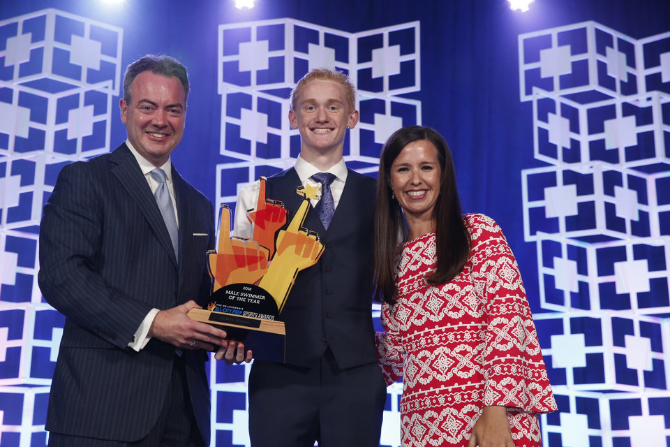 Photo - Oklahoman Publisher Chris Reen and sports columnist Jenni Carlson present the male swimmer of the year award to Aiden Hayes at the Oklahoman's All-City Prep Sports Awards, celebrating top high school athletes, at the Cox Convention Center on Tuesday, June 26, 2018 in Oklahoma City, Okla.  Photo by Steve Sisney, The Oklahoman