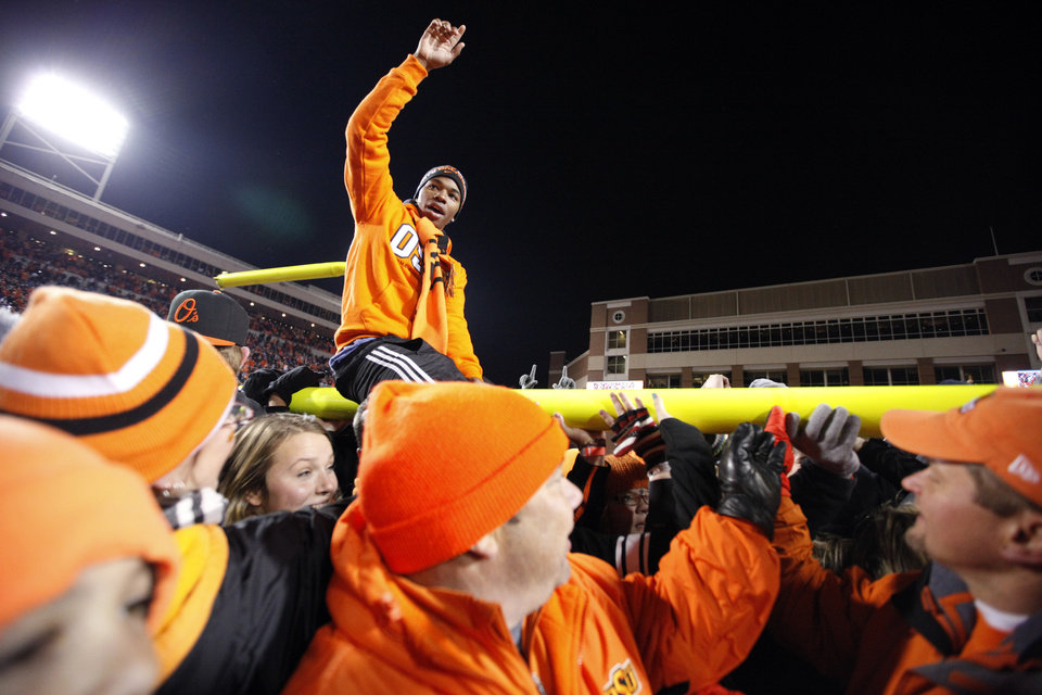 Photo - Fans celebrate following the Bedlam college football game between the Oklahoma State University Cowboys (OSU) and the University of Oklahoma Sooners (OU) at Boone Pickens Stadium in Stillwater, Okla., Saturday, Dec. 3, 2011. OSU won 44-10. Photo by Sarah Phipps, The Oklahoman