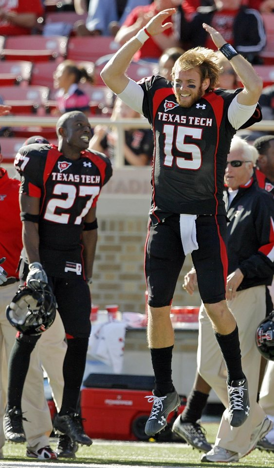 Photo - Texas Tech quarterback Taylor Potts (15) leaps in the air next to Edward Britton (27) as the song
