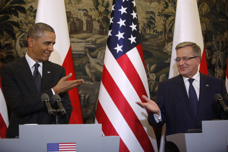 Photo - U.S. President Barack Obama and Poland's President Bronislaw Komorowski gesture towards each other at a news conference at Belweder Palace in Warsaw, Poland, Tuesday, June 3, 2014. (AP Photo/Charles Dharapak)