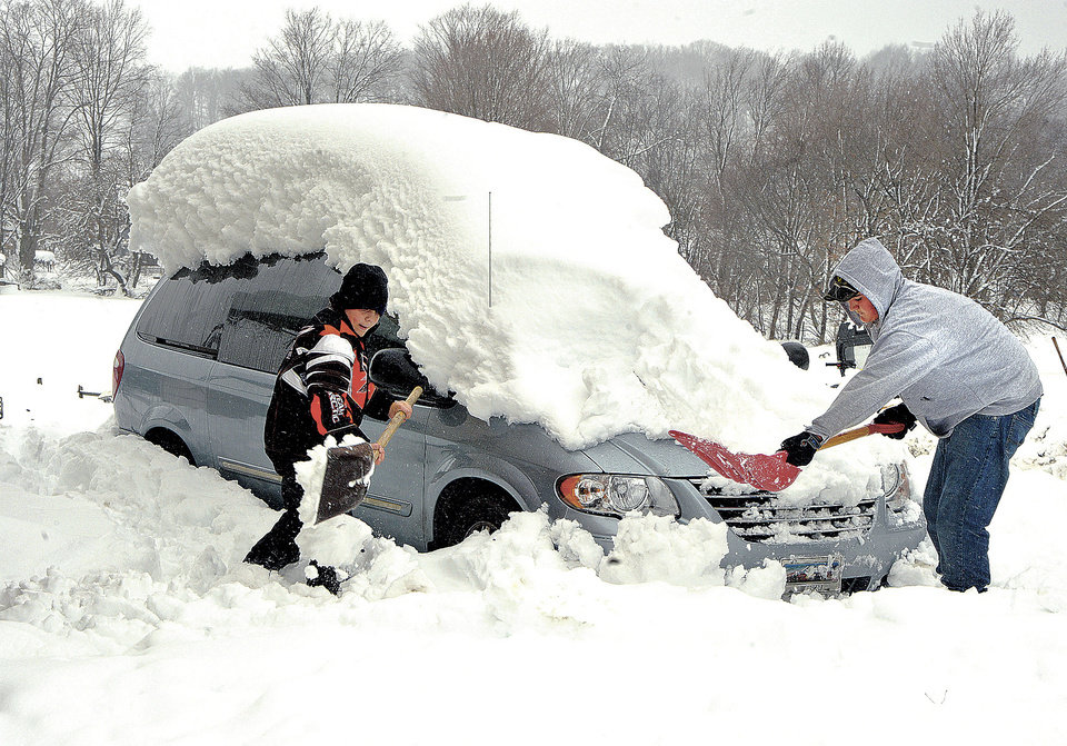 Photo -   Ryan Auvil and his brother Nick shovel snow in the driveway of their house Thursday, Nov. 1, 2012, to get their car out after the recent storm left 3 feet of snow in Aurora, W.Va., with more snow in the forecast. (AP Photo/The Dominion Post, Ron Rittenhouse)