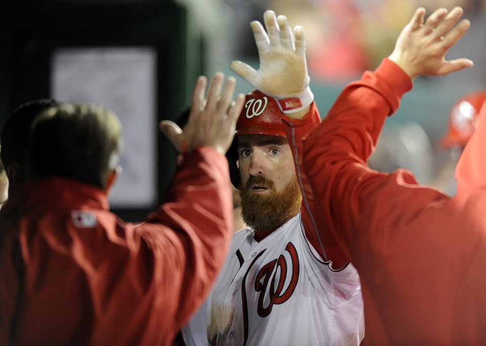 Photo - Washington Nationals' Adam LaRoche, center, reacts in the dugout after he scored on a single by Anthony Rendon during the sixth inning of a baseball game against the Miami Marlins, Tuesday, April 8, 2014, in Washington. The Nationals won 5-0. (AP Photo/Nick Wass)