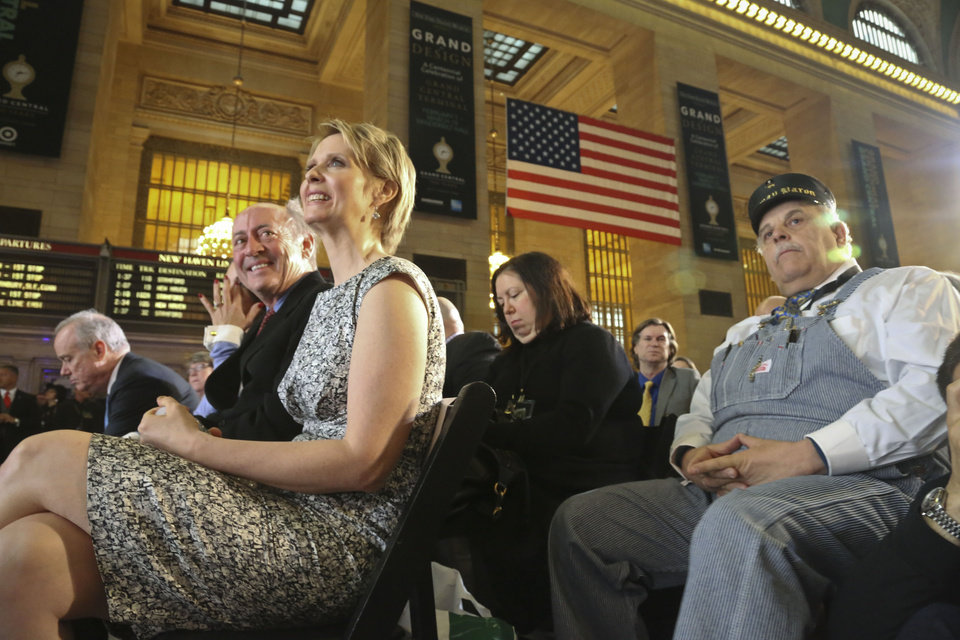 Photo - New York poet Billy Collins, second from left, Broadway star Cynthia Nixon, third from left, and retired Amtrak conductor Tom Savio, right, are among invited guests attending the Grand Central Terminal centennial celebration on Friday, Feb. 1, 2013 in New York. Grand Central, once in danger of being demolished, is celebrating its 100th birthday with speeches, a brass band and a rollback to 1913 prices when a slice of cheesecake might go for 19 cents. The majestic Beaux Arts building, known as Grand Central station although it is technically a terminal, is one of the world's most popular tourist destinations.   (AP Photo/Bebeto Matthews)