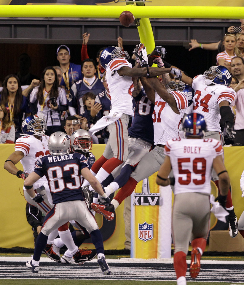 Photo - New York Giants safety Kenny Phillips (21) and linebacker Jacquian Williams (57) fight for control of the ball with New England Patriots tight end Aaron Hernandez (81) during the second half of the NFL Super Bowl XLVI football game, Sunday, Feb. 5, 2012, in Indianapolis. The Giants won 21-17. (AP Photo/David Duprey) ORG XMIT: SB474