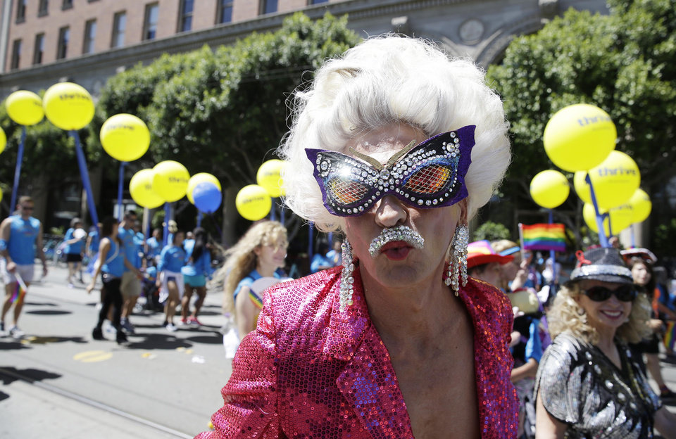 Photo - A man dressed in drag marches with a group of employees and family members with Kaiser Permanente during the 44th annual San Francisco Gay Pride parade Sunday, June 29, 2014, in San Francisco. The lesbian, gay, bisexual, and transgender celebration and parade is one of the largest LGBT gatherings in the nation. (AP Photo/Eric Risberg)