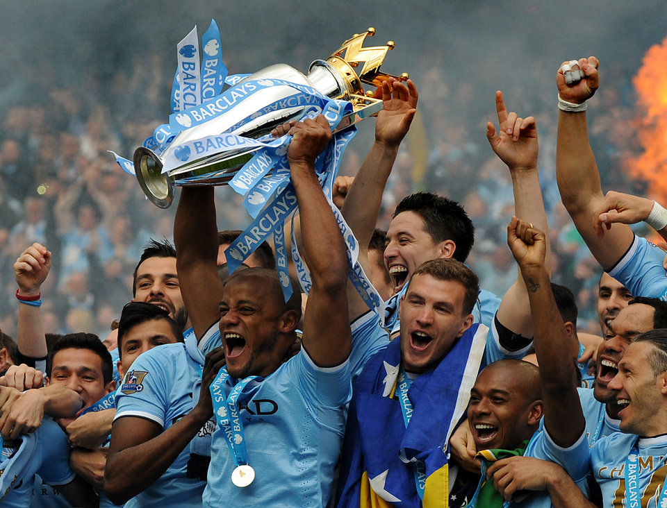 Photo - Manchester City's players captain Vincent Kompany, center, holds the Cup and celebrates with teammates after being crowned Premier League Champions, after the English Premier League soccer match between Manchester City and West Ham United at the Etihad Stadium,  Manchester, England, Sunday, May 11, 2014. (AP Photo/Rui Vieira)