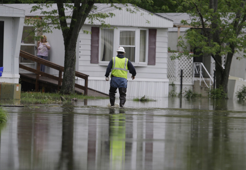 Photo - A Vectren employee makes his way through floodwaters to turn off power to mobile homes in the Pleasant Ridge Mobile Home Park in Evansville, Ind., Wednesday, April 27, 2011. (AP Photo/Darron Cummings)