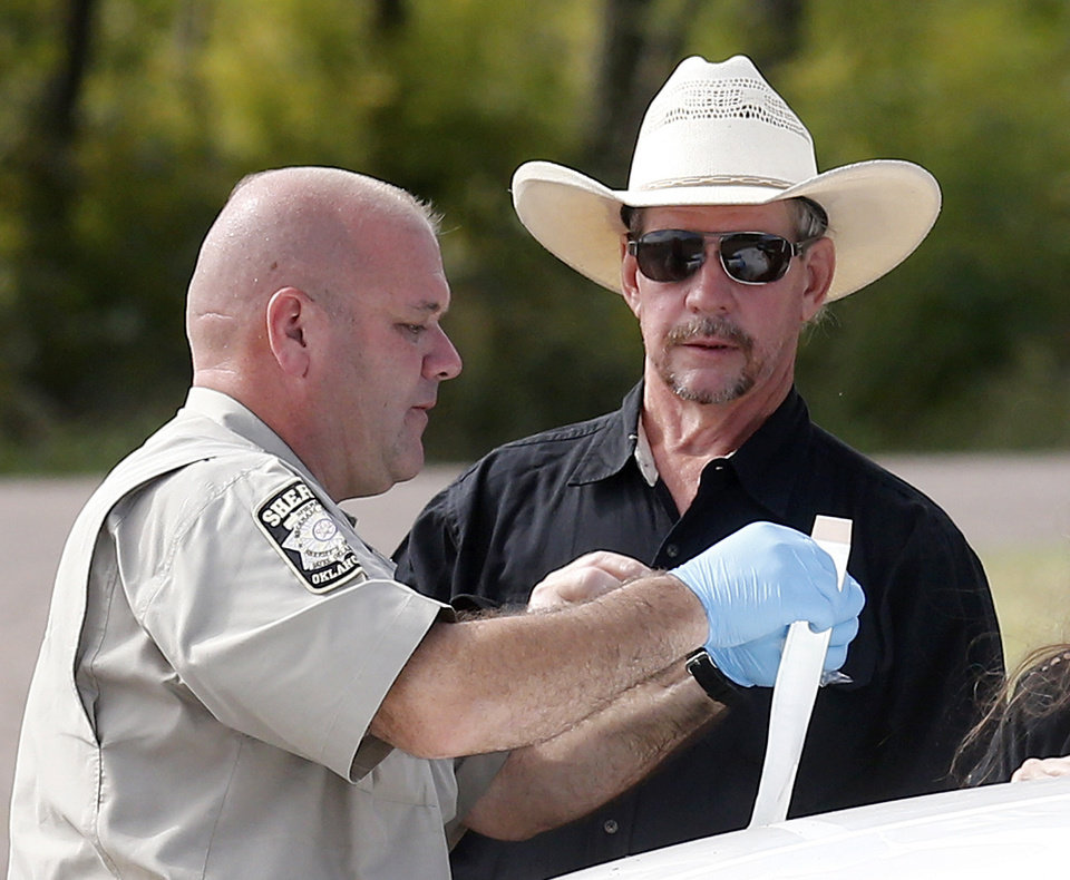 Photo - Tim Porter, right, talks with Beckham County Sheriff's Deputy J. Kessel, left, after giving a DNA sample at the scene where two cars were found in Foss Lake, in Foss, Okla., Wednesday, Sept. 18, 2013. Porter says he believes his grandfather's remains may be in one of the cars. The Oklahoma State Medical ExaminerÂ's Office says authorities have recovered skeletal remains of multiple bodies in the Oklahoma lake where the cars were recovered. (AP Photo/Sue Ogrocki) ORG XMIT: OKSO103