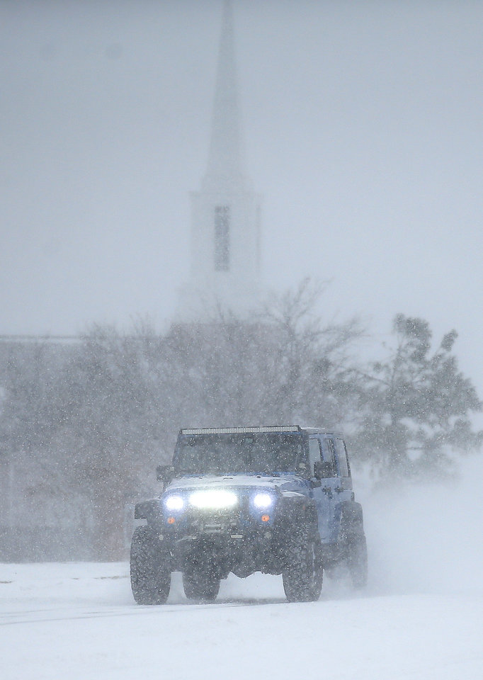 Photo - A car travels north on N. Pennsylvania Ave. near NW 150 in Oklahoma City, Sunday, Feb. 14, 2021. [Sarah Phipps/The Oklahoman]