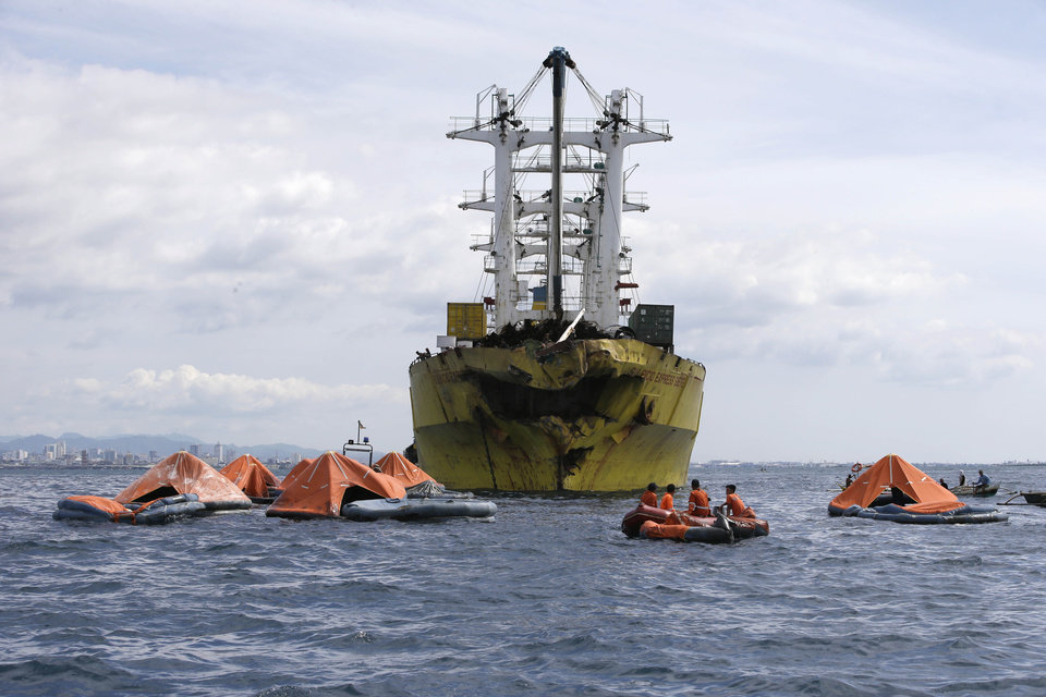 Photo - A cluster of life rafts floate near the cargo ship Sulpicio Express Siete with its damaged bow a day after it collided with a passenger ferry off the waters of Talisay city, Cebu province in central Philippines, Saturday Aug. 17, 2013. Divers combed through a sunken ferry Saturday to retrieve the bodies of more than 200 people still missing from an overnight collision with a cargo vessel near the central Philippine port of Cebu that sent passengers jumping into the ocean and leaving many others trapped. At least 28 were confirmed dead and hundreds rescued. The captain of the ferry MV Thomas Aquinas, which was approaching the port late Friday, ordered the ship abandoned when it began listing and then sank just minutes after collision with the MV Sulpicio Express, coast guard deputy chief Rear Adm. Luis Tuason said. (AP Photo/Bullit Marquez)