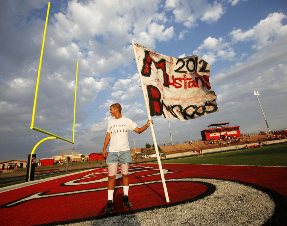 Mustang senior Patrick Osborne holds the flag he will carry when he runs with the Broncos onto the field before a high school football game between Mustang and Putnam City North in Mustang, Okla., Friday, Sept. 7, 2012. Photo by Nate Billings, The Oklahoman