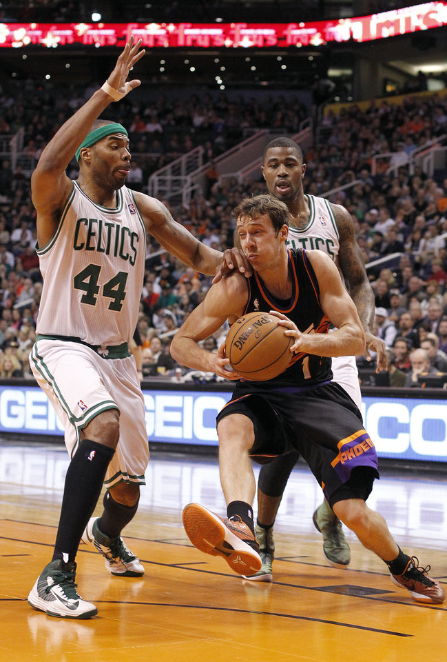 Phoenix Suns guard Goran Dragic, center, of Slovenia, drives to the basket around Boston Celtics forward Chris Wilcox, left, and Terrence Williams, right, in the second half of an NBA basketball game, Friday, Feb. 22, 2013, in Phoenix. The Celtics won 113-88. (AP Photo/Paul Connors)