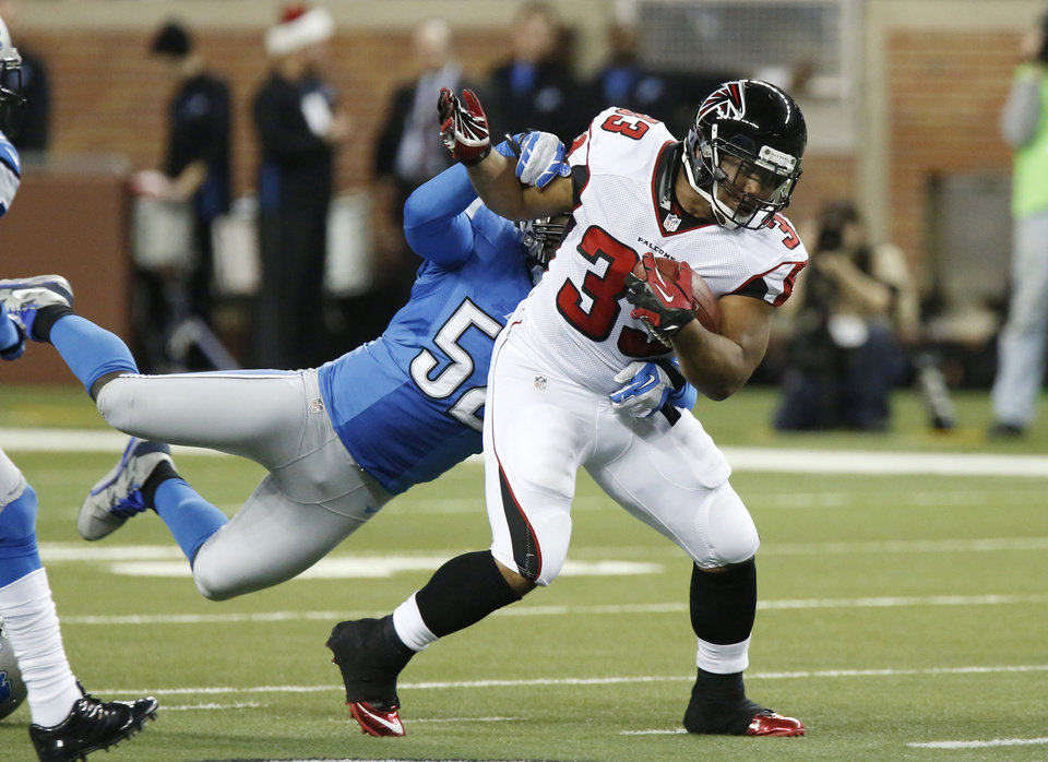Atlanta Falcons running back Michael Turner (33) breaks a tackle from Detroit Lions outside linebacker Justin Durant (52) during the first quarter of an NFL football game at Ford Field in Detroit, Saturday, Dec. 22, 2012. (AP Photo/Duane Burleson)