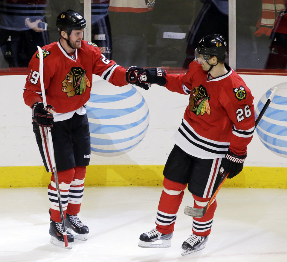 Photo - Chicago Blackhawks' Bryan Bickell, left, celebrates with Michal Handzus (26) after scoring against the Anaheim Ducks during the third period of an NHL hockey game in Chicago, Friday, Jan. 17, 2014. The Blackhawks won 4-2. (AP Photo/Nam Y. Huh)