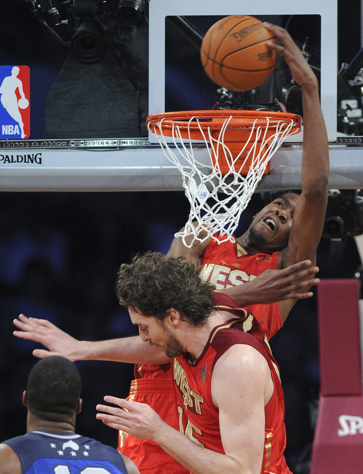West's Pau Gasol, of the Los Angeles Lakers, tries to avoid Kevin Durant, of the Oklahoma City Thunder, who dunks during the first half of the NBA basketball All-Star Game on Sunday, Feb. 20, 2011, in Los Angeles.  (AP Photo/Mark J. Terrill)