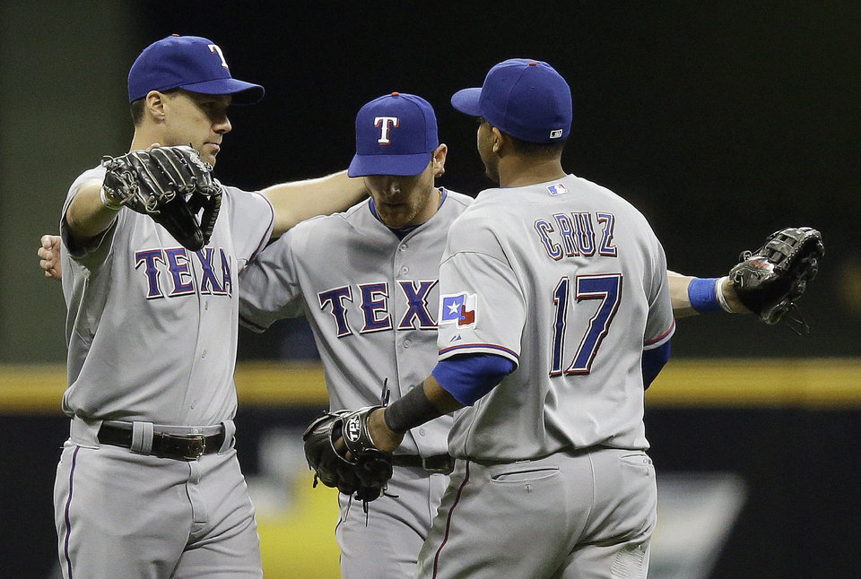 Photo - Texas Rangers' David Murphy, from left, Craig Gentry and Nelson Cruz (17) celebrate after a baseball game against the Milwaukee Brewers Wednesday, May 8, 2013, in Milwaukee. The Rangers won 4-1. (AP Photo/Morry Gash)