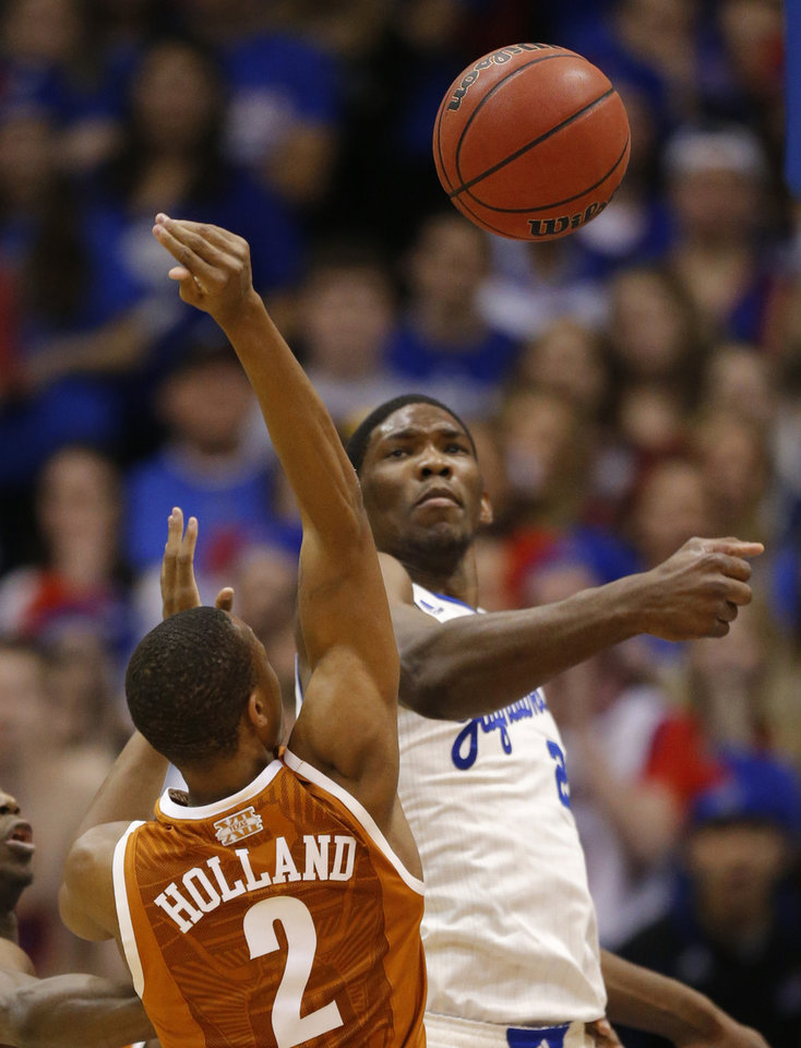 Photo - Kansas center Joel Embiid, right, blocks a shot by Texas guard Demarcus Holland (2) during the first half of an NCAA college basketball game in Lawrence, Kan., Saturday, Feb. 22, 2014. (AP Photo/Orlin Wagner)