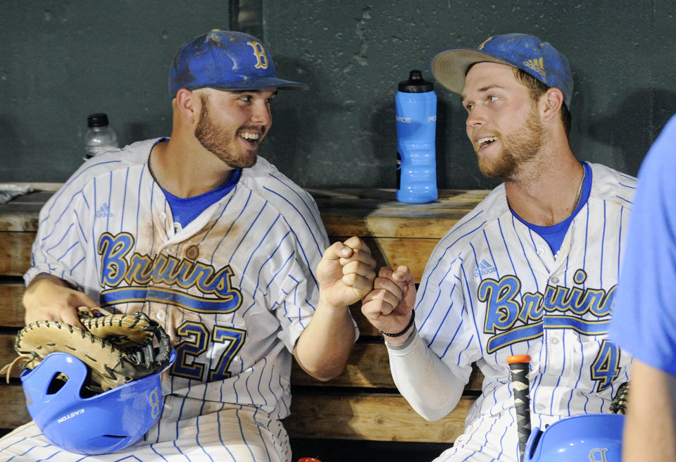 UCLA's Pat Gallagher (27) and Eric Filia (4) bump fists in the dugout after winning 4-1 against North Carolina in an NCAA College World Series baseball game in Omaha, Neb., Friday, June 21, 2013. (AP Photo/Francis Gardler)