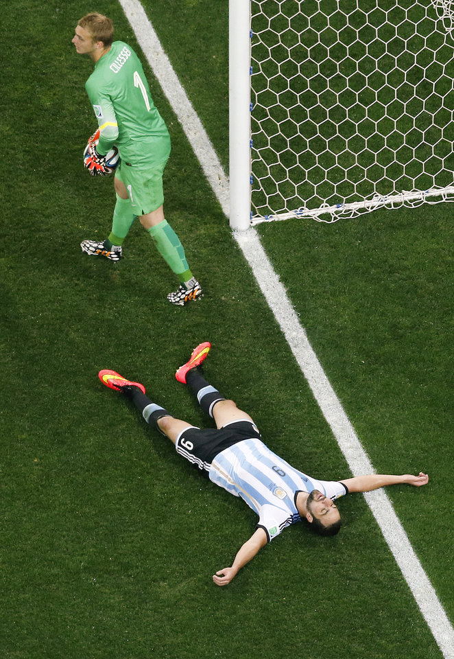 Photo - Argentina's Gonzalo Higuain lies on the pitch after missing a chance as Netherlands' goalkeeper Jasper Cillessen (1) holds the ball during the World Cup semifinal soccer match between the Netherlands and Argentina at the Itaquerao Stadium in Sao Paulo, Brazil, Wednesday, July 9, 2014. (AP Photo/Fabrizio Bensch, Pool)
