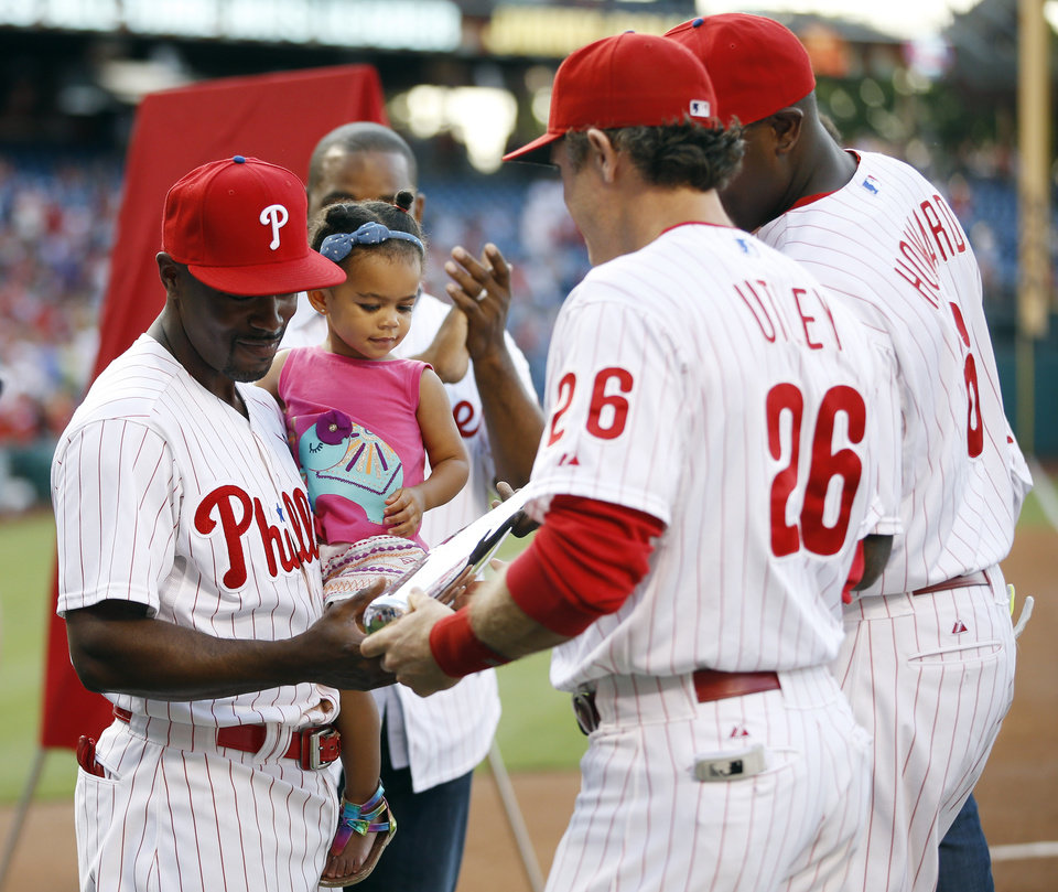 Photo - Philadelphia Phillies' Jimmy Rollins, left, is presented with a commemorative bat by teammates Chase Utley, center, and Ryan Howard during a ceremony honoring him for becoming the franchise hits leader before a baseball game against the Miami Marlins, Monday, June 23, 2014, in Philadelphia. (AP Photo/Matt Slocum)