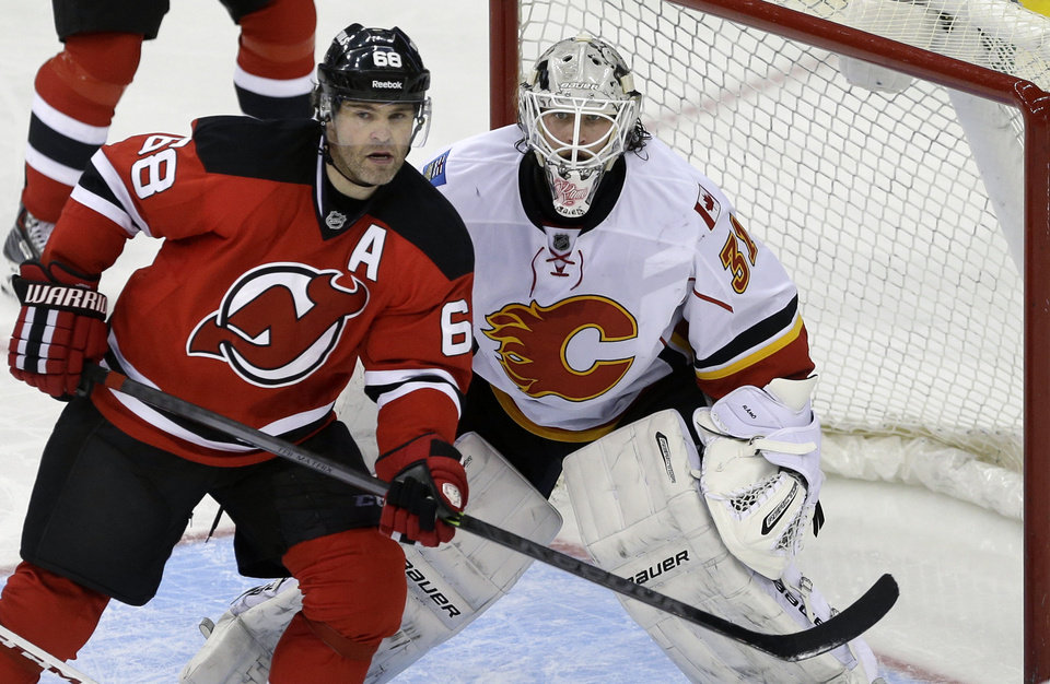 Photo - New Jersey Devils' Jaromir Jagr (68), of the Czech Republic, plays in front of Calgary Flames goalie Karri Ramo (31), of Finland, during the third period of an NHL hockey game in Newark, N.J., Monday, April 7, 2014. The Flames won 1-0. (AP Photo/Mel Evans)