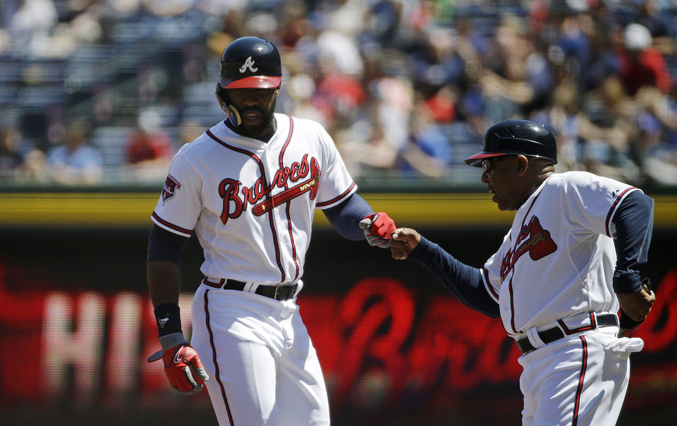 Photo - Atlanta Braves' Jason Heyward, left, is fist-bumped by first base coach Terry Pendleton after hitting a single in the first inning of a baseball game against the Miami Marlins, Wednesday, April 23, 2014, in Atlanta. (AP Photo/David Goldman)