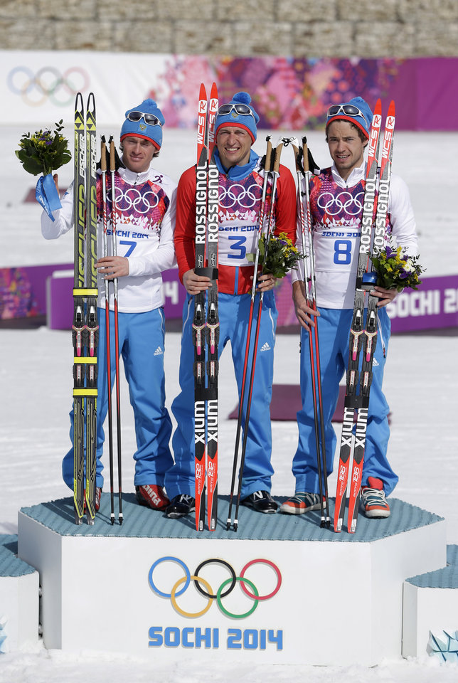 Photo - Russia's gold medal winner Alexander Legkov is flanked by Russia's silver medal winner Maxim Vylegzhanin, left and Russia's bronze medal winner Ilia Chernousov during the flower ceremony of the men's 50K cross-country race at the 2014 Winter Olympics, Sunday, Feb. 23, 2014, in Krasnaya Polyana, Russia. (AP Photo/Matthias Schrader)
