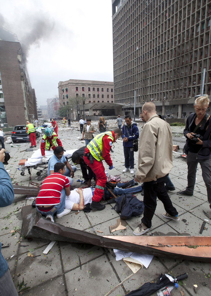 Photo - People are treated at the scene after an explosion in Oslo, Norway, Friday July 22, 2011. A loud explosion shattered windows Friday at the government headquarters in Oslo which includes the prime minister's office, injuring several people.  Prime Minister Jens Stoltenberg is safe, government spokeswoman Camilla Ryste told The Associated Press. (AP PHOTO / Holm Morten, Scanpix) NORWAY OUT  ORG XMIT: LON812