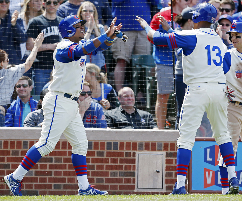 Photo - Chicago Cubs' Luis Valbuena, left, and Starlin Castro, right, celebrate after scoring on Nate Schierholtz's triple against the Miami Marlins during the sixth inning of a baseball game on Sunday, June 8, 2014, in Chicago. (AP Photo/Andrew A. Nelles)