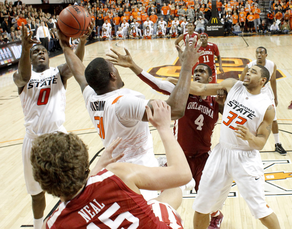 Photo - Oklahoma State's Jean-Paul Olukemi (0),  Matt Pilgrim (31), and Marshall Moses (33) fight for the ball with Oklahoma's Andrew Fitzgerald (4) during the Bedlam men's college basketball game between the University of Oklahoma Sooners and Oklahoma State University Cowboys at Gallagher-Iba Arena in Stillwater, Okla., Saturday, February, 5, 2011. Photo by Bryan Terry, The Oklahoman