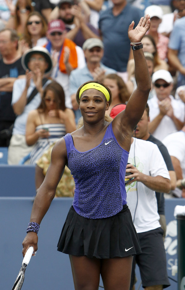 Photo - Serena Williams waves to the crowd after defeating Caroline Wozniacki, from Denmark,  2-6, 6-2, 6-4 in a semifinal match at the Western & Southern Open tennis tournament, Saturday, Aug. 16, 2014, in Mason, Ohio.  (AP Photo/David Kohl)