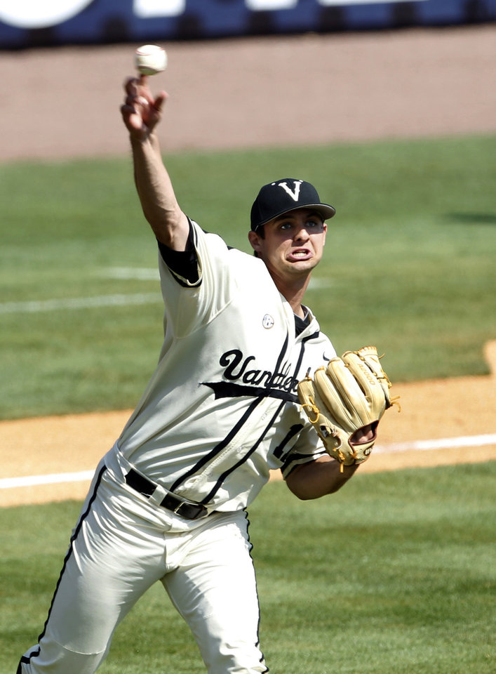 Photo - Vanderbilt's Tyler Beede (11) throws to first base after fielding a bunt against Mississippi during the second inning at the Southeastern Conference NCAA college baseball tournament on Thursday, May 22, 2014, in Hoover, Ala. (AP Photo/Butch Dill)