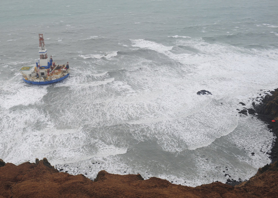 Photo - This aerial image provided by the U.S. Coast Guard shows the Royal Dutch Shell drilling rig Kulluk aground off a small island near Kodiak Island Tuesday Jan. 1, 2013. No leak has been seen from the drilling ship that grounded off the island during a storm, officials said Wednesday, as opponents criticized the growing race to explore the Arctic for energy resources. (AP Photo/U.S. Coast Guard)