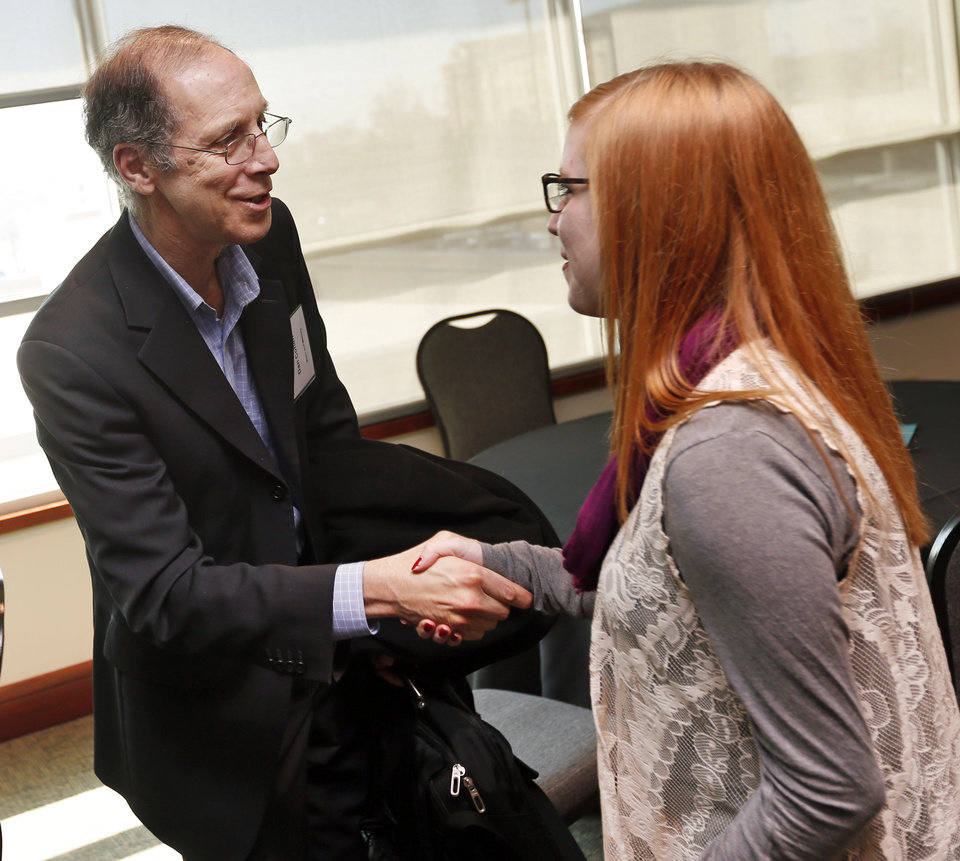 Photo - Dan Cohen, executive director of Music and Memory, left, shakes hands with Emily Wilkerson, 17, an honor student from Blanchard, before a showing of the documentary