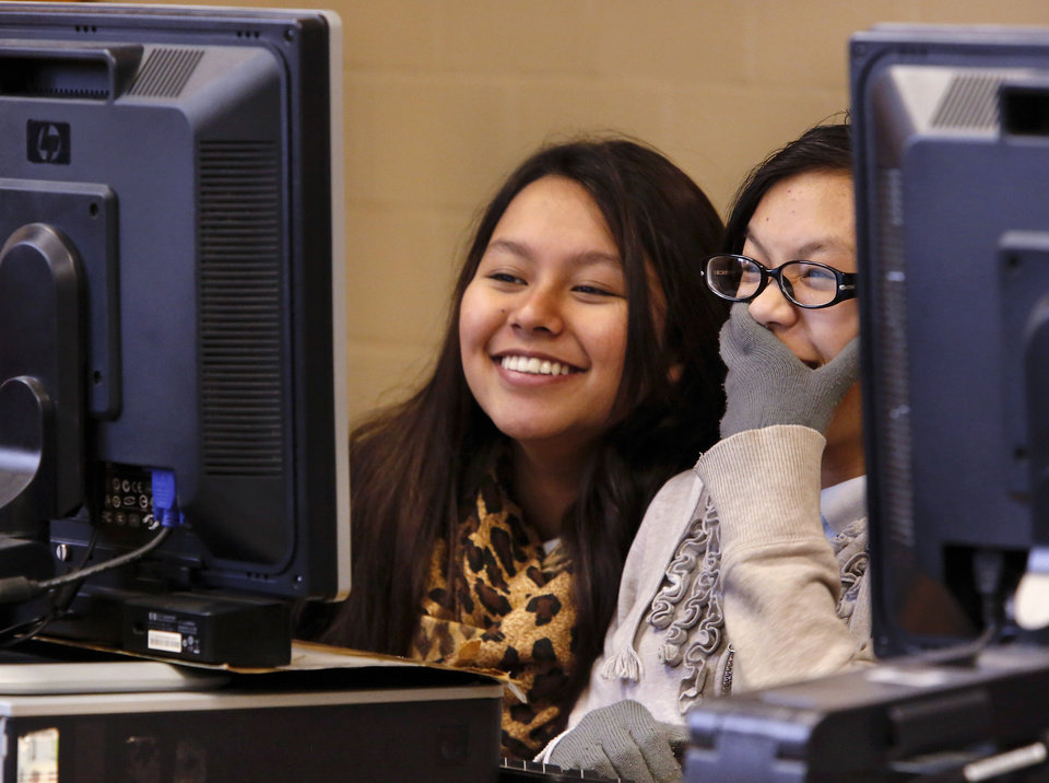 Two girls laugh when they discover one of their mistakes while working together on a project in Coach Shea Stark's computer class at Taft Middle School on Thursday, Jan. 30, 2014. Story about high poverty in the Oklahoma City school district and how it can affect the  learning process if a child comes to class  hungry, not clothed properly or without adequate sleep due to issues related to poverty. Photo by Jim Beckel, The Oklahoman