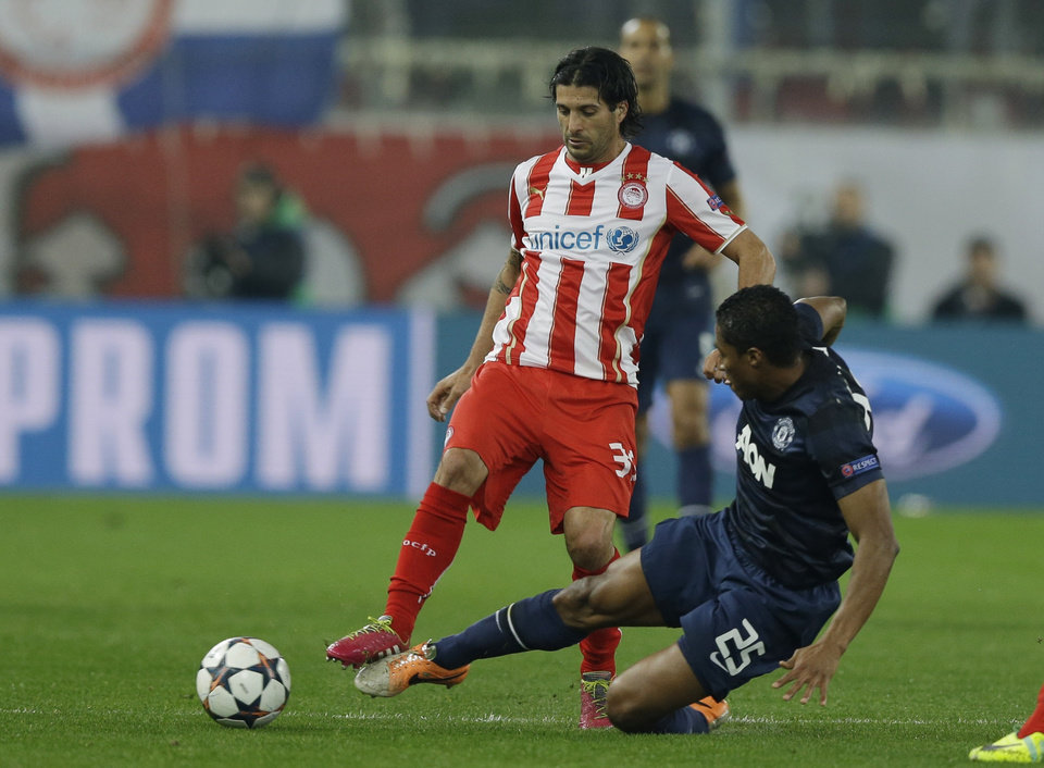 Photo - Olympiakos' Alejandro Dominguez, left, fights for the ball with Manchester United's Antonio Valencia during their Champions League, round of 16, first leg soccer match at Georgios Karaiskakis stadium, in Piraeus port, near Athens, on Tuesday, Feb. 25, 2014. (AP Photo/Thanassis Stavrakis)