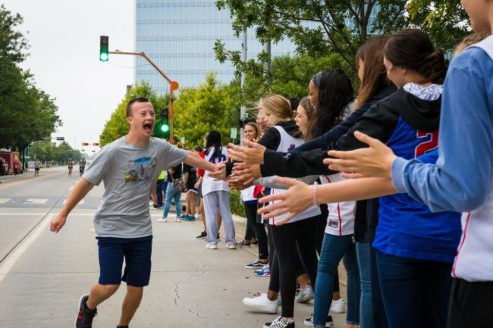Photo -  Runner and self-advocate Ayden Little high-fives the spirit volunteers as he finishes the 2019 Down Syndrome 5K. [PHOTO PROVIDED]